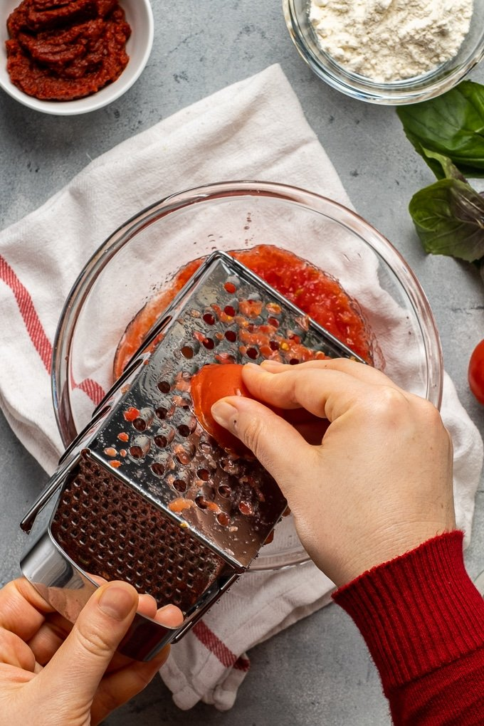 Woman hands grating tomatoes to make soup.