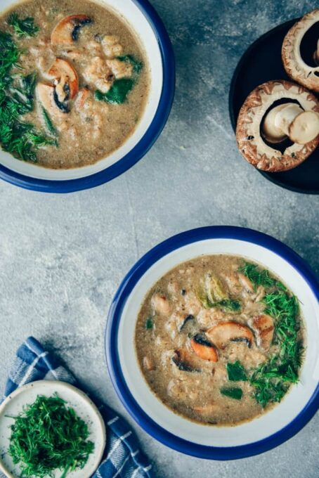 Vegan cream of mushroom soup in bowls and mushrooms accompany.