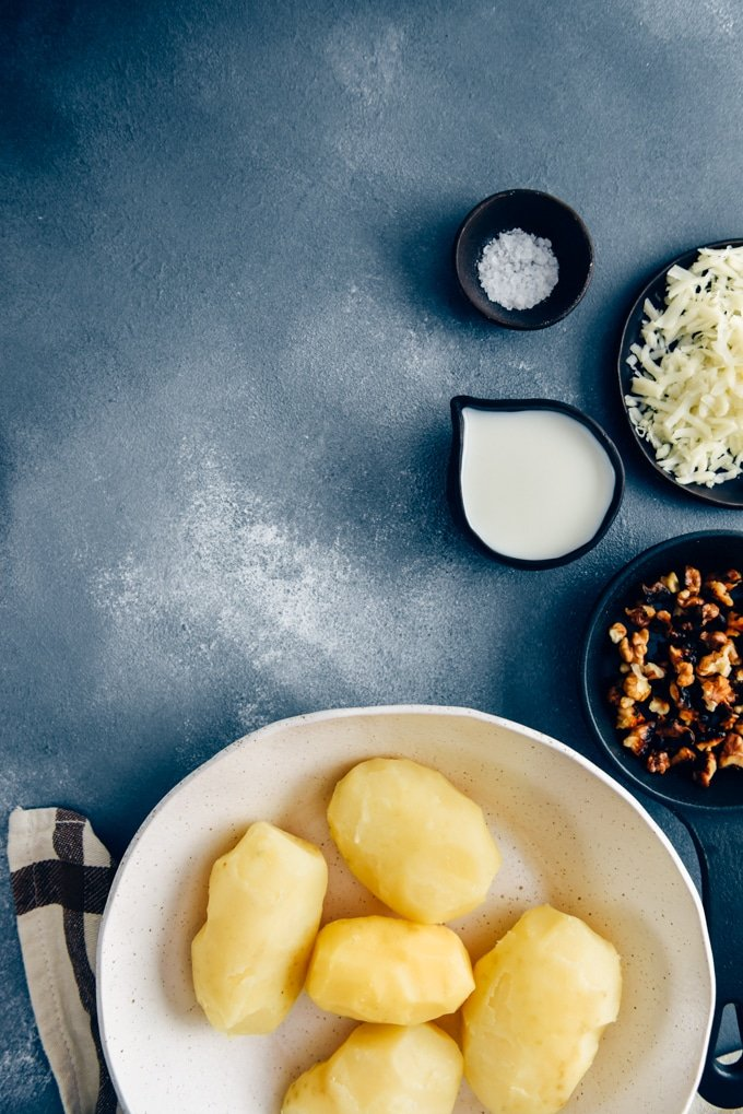 Cooked and peeled potatoes in a white ceramic bowl for cheesy mashed potatoes on a dark background.