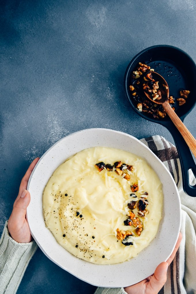 Hands holding cheesy mashed potatoes with roasted walnuts and black pepper in a white ceramic bowl