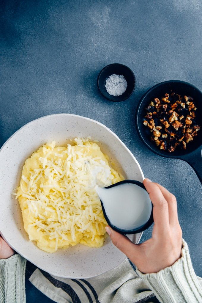 Hands pouring milk from a black ceramic cup on mashed potatoes .