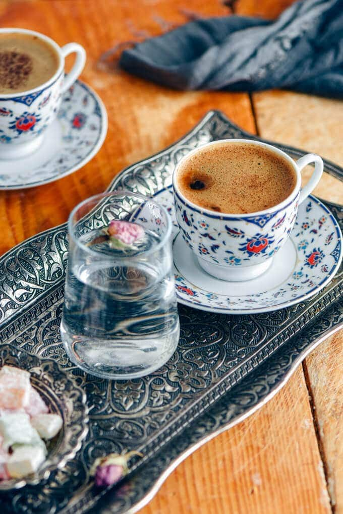 Turkish coffee served in a traditional cup on a copper coffee tray photographed with a glass of water and turkish delights on the side.