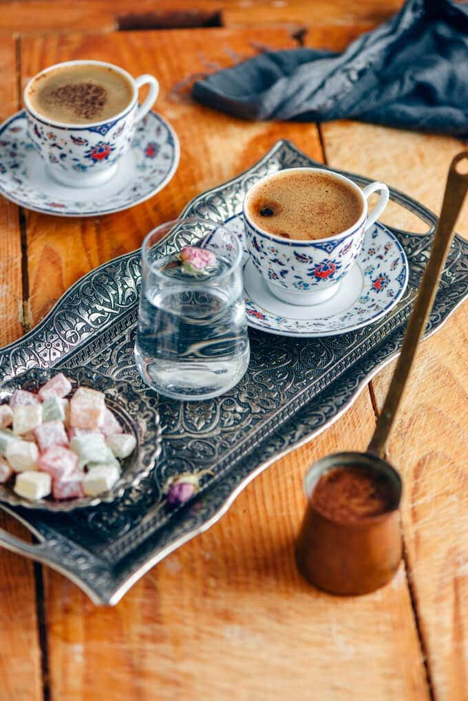 Turkish coffee served in traditional turkish coffee cups with a glass of water and turkish delights on the side.