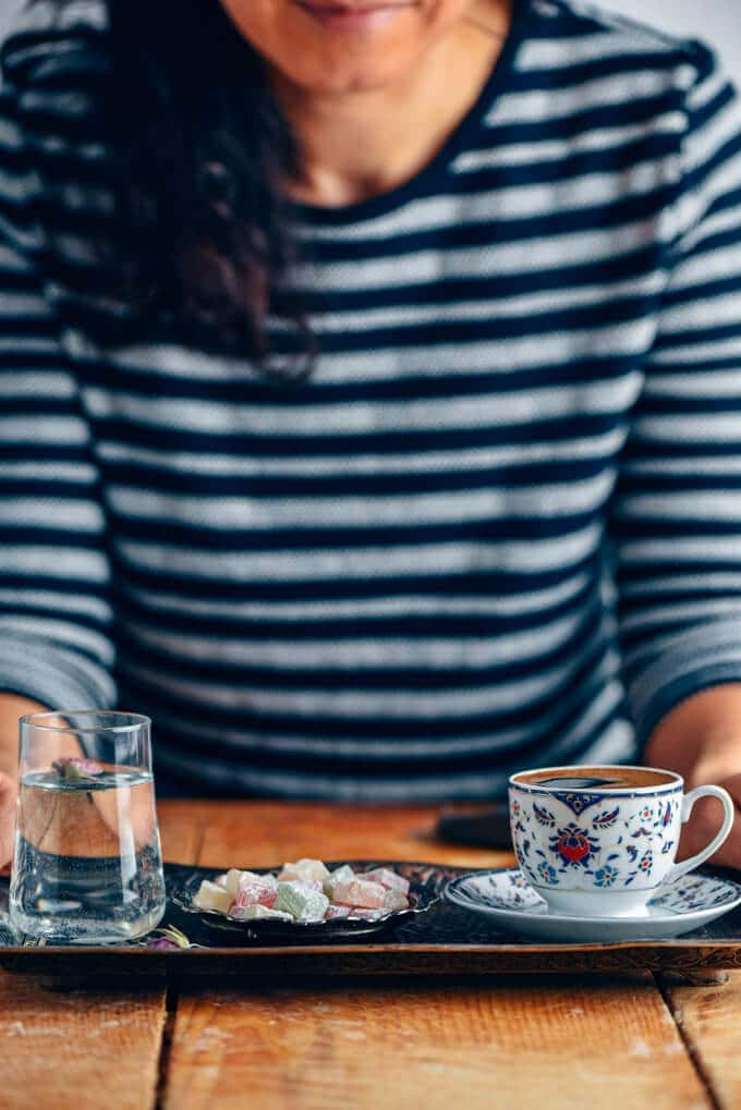 A woman photographed serving Turkish coffee in a copper tray accompanied by Turkish delights and a glass of water.