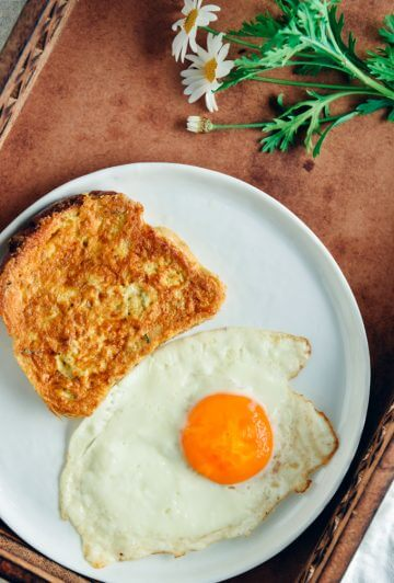 French toast with a fried egg on the side for breakfast and spring flowers accompany.