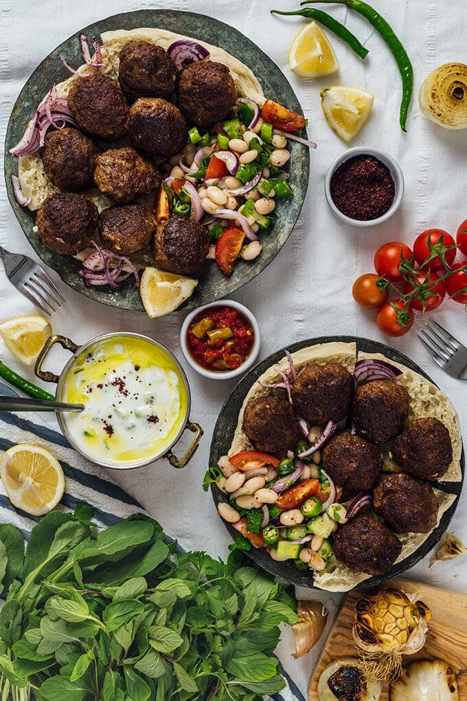 Best Turkish kofte on copper plates with bean salad and cucumber dip