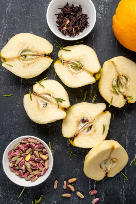 Peeled and halved quince fruit, pistachios, hibiscus leaves and orange on a dark background.