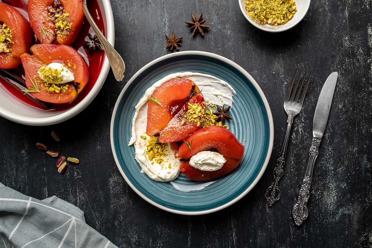 Poached quince fruit served on a plate with pistachios and clotted cream, a white pan with the rest of the quinces, a knife and a fork on the side.