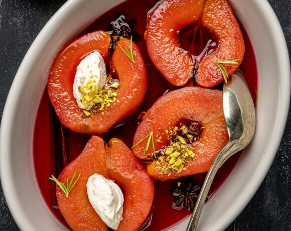 Poached quinces in a white baking pan topped with crumbled pistachio and clotted cream, with a spoon in it.