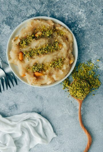 Turkish flour halva recipe topped with ground pistachio served on a white plate.