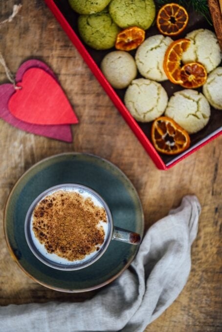 A cup of Turkish salep garnished with cinnamon powder photographed on a wooden background. Accompanied by red heart shaped ornaments, a box full of cookies, cinnamon sticks and orange chips.