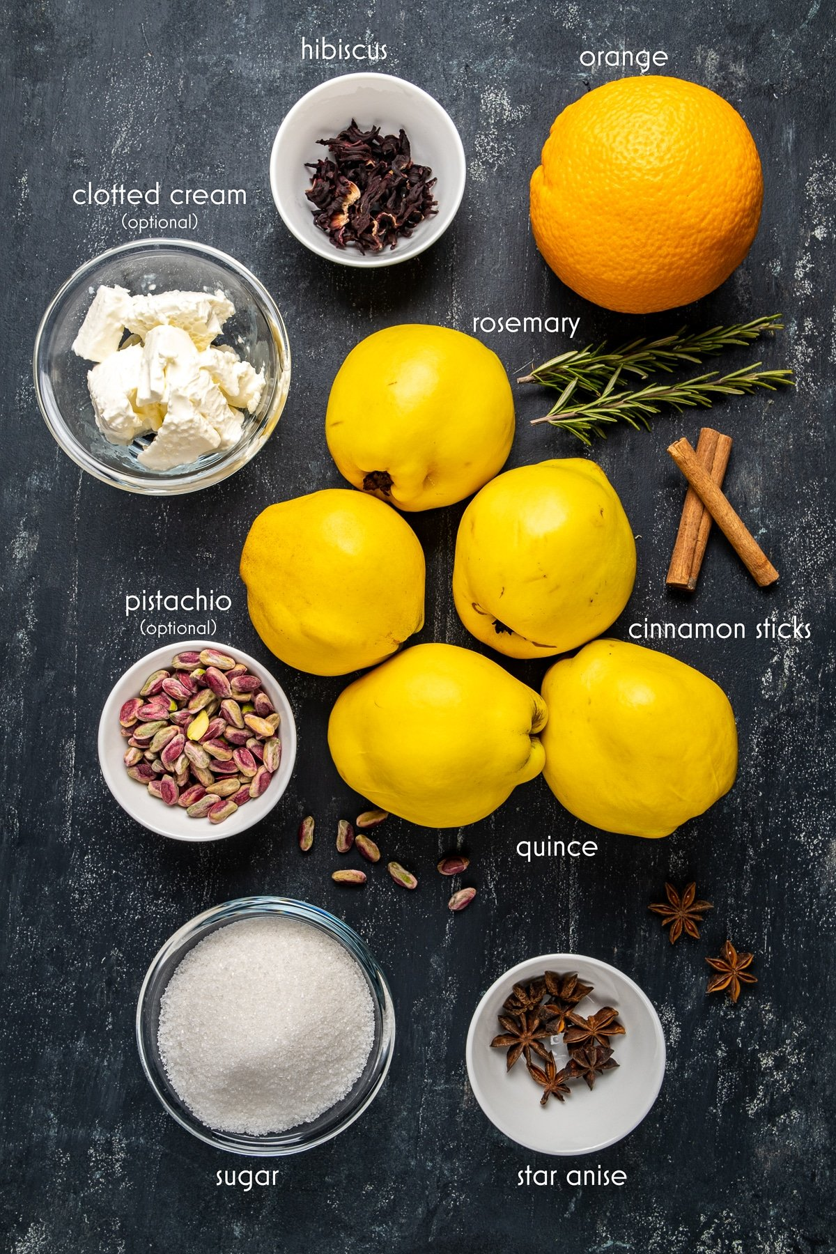 Quinces, cinnamon sticks, rosemary sprigs, orange, sugar, pistachio, hibiscus, star anise, clotted cream are all on a dark background.