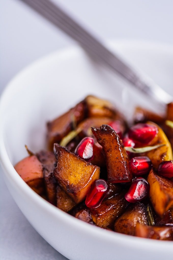easy apple cinnamon compote with pomegranate arils in a white bowl