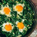 Fried eggs with spinach in a cast iron skillet