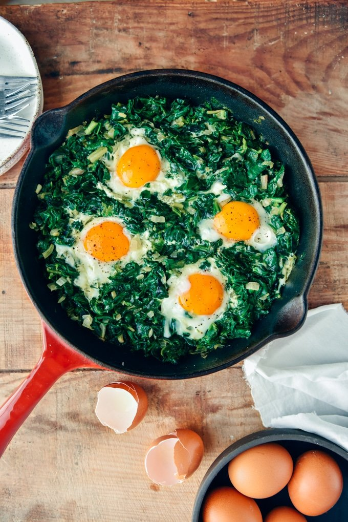 Eggs with spinach in a cast iron skiller