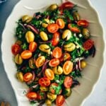Green olive salad with tomatoes and herbs in a salad bowl