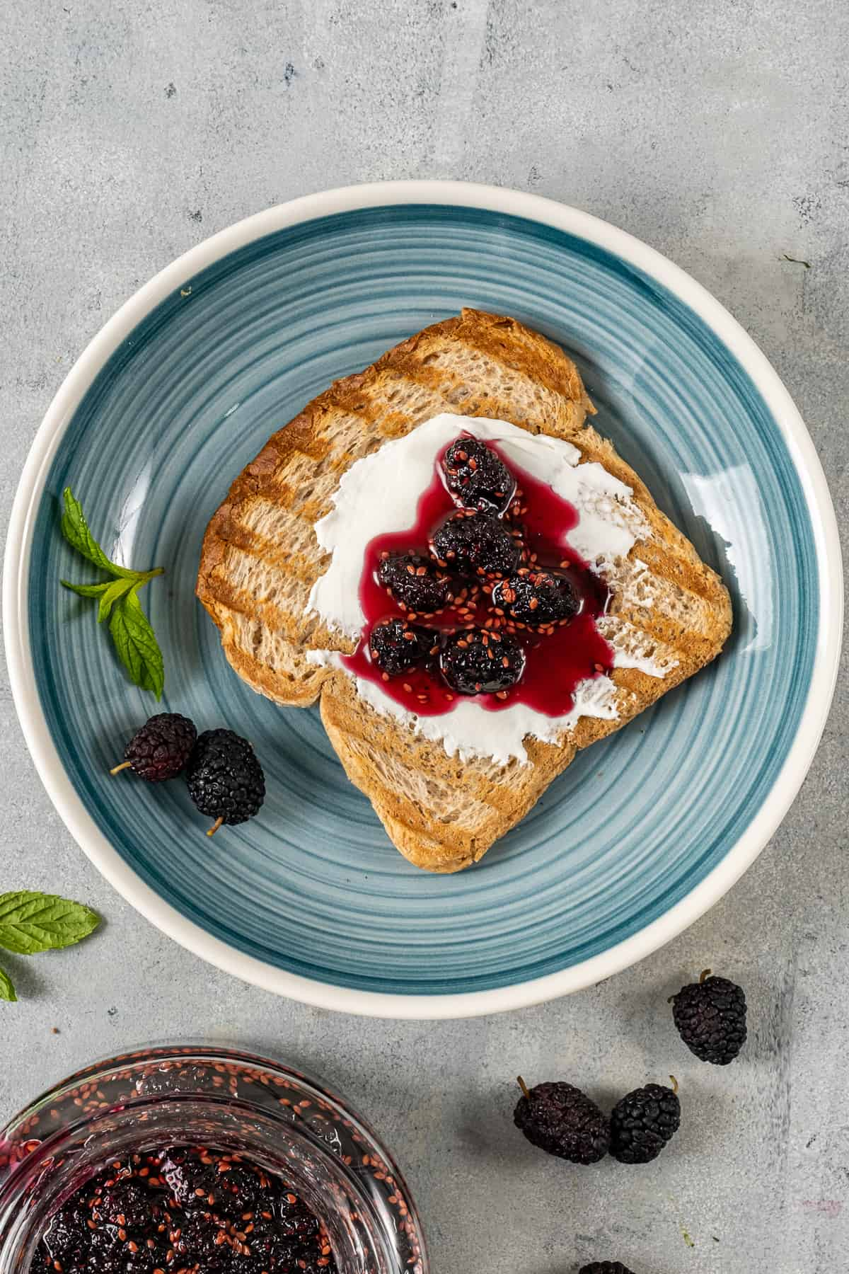Toasted bread topped with cream cheese and mulberry jam on a blueish plate.