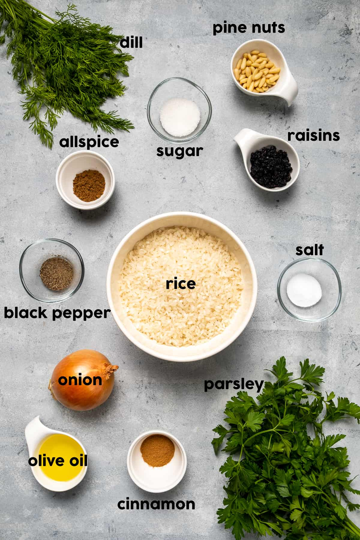 Rice in a large bowl, pine nuts, raisins, dill and parsley, spices, onion and olive oil on a grey background.