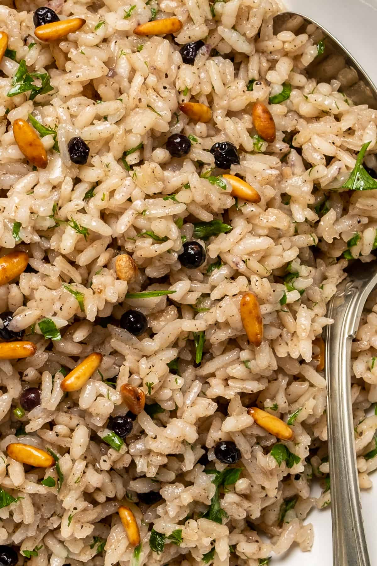 Allspice rice pilaf with raisins, pine nuts and parsley and a spoon in it.