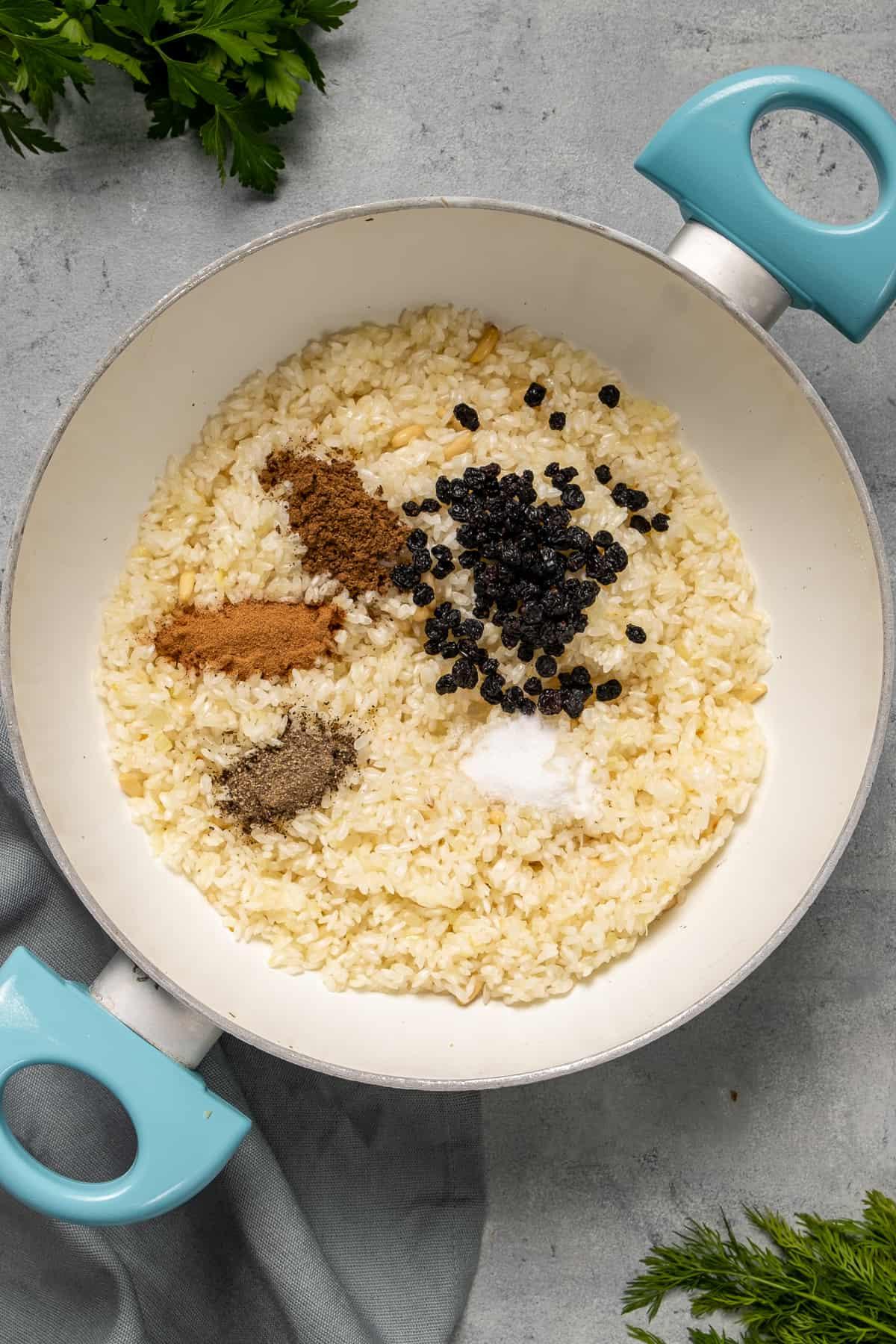 Rice, currant raisins, allspice, cinnamon, salt and pepper in a white pan.