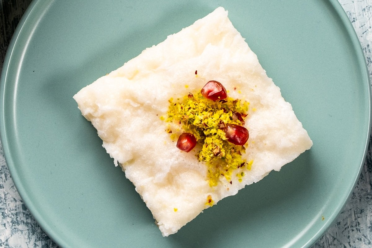 A slice of gullac dessert topped with ground pistachio and pomegranate arils.