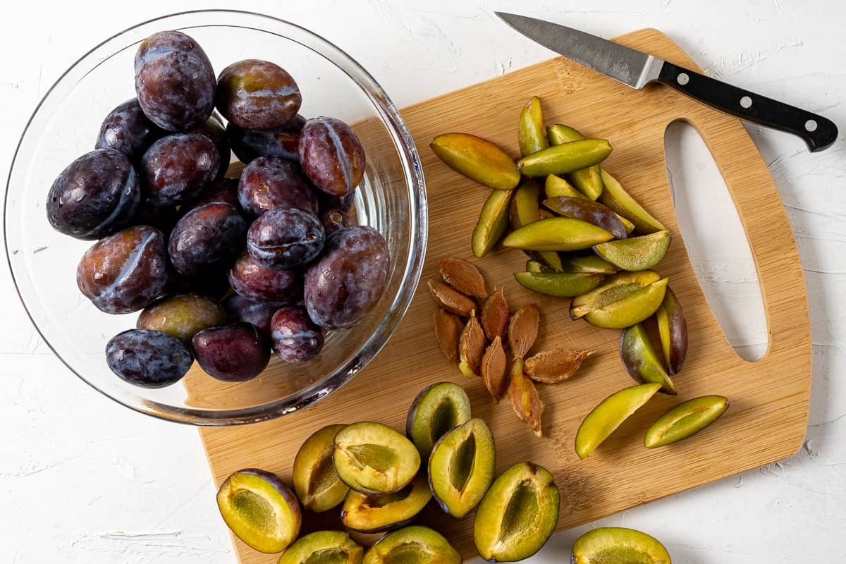 Chopped damson plums on a wooden board with a knife on the side and whole plums in a large glass bowl.