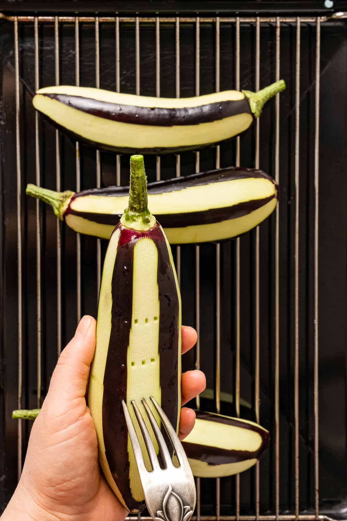 Hands pricking an eggplant with a fork and more eggplants on a grilling rack.
