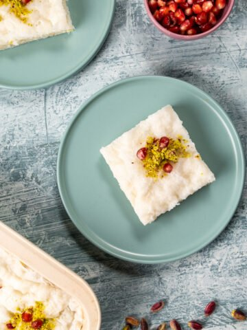 A slice of gullac dessert on two pastel colored plates on a light background, a bowl of pomegranate arils on the side.