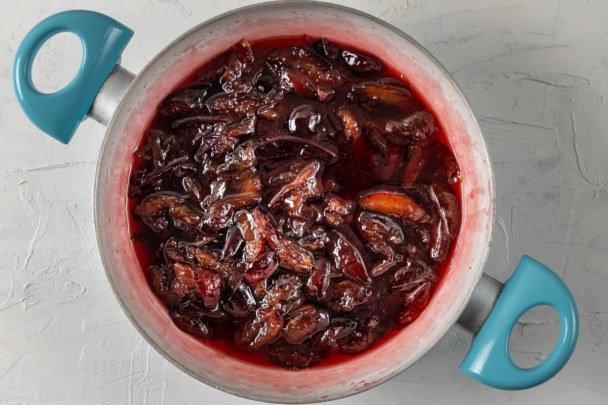 Damson plum jam with its beautiful red color in a pan.