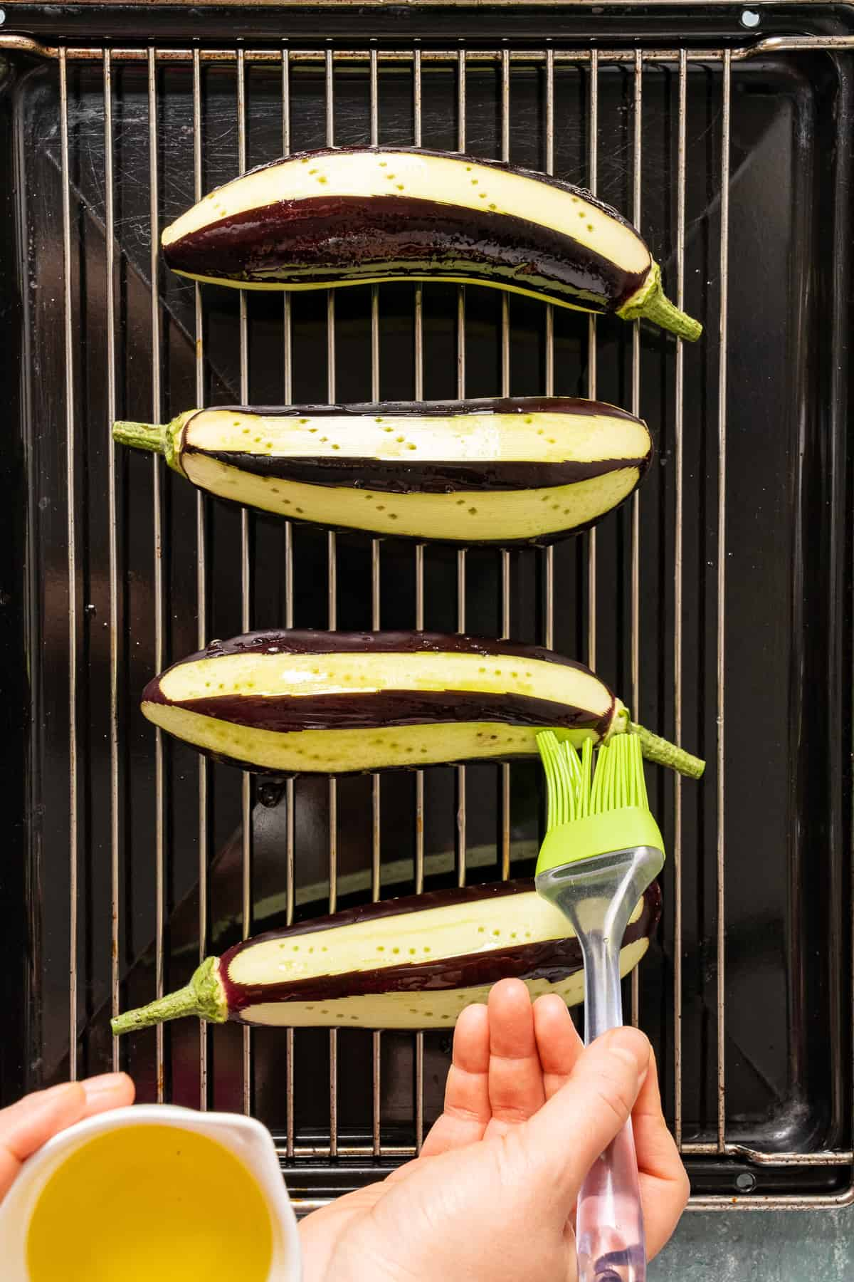 Hands oiling eggplants on a grilling rack with a brush.