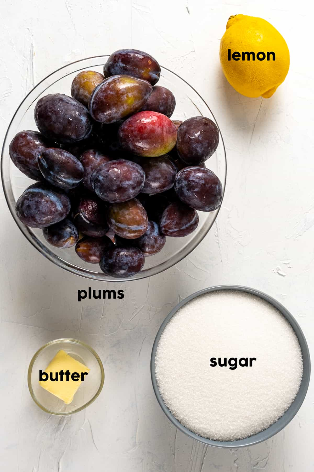 Fresh plums in a large bowl, lemon, sugar and butter on the side.