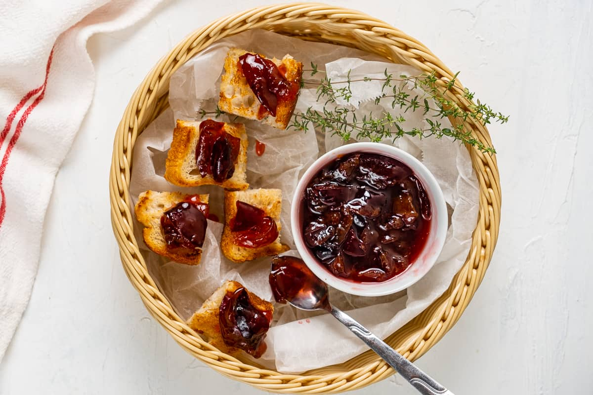 Plum jam served in a small white bowl with toasted bread bites topped with jam all in a basket.