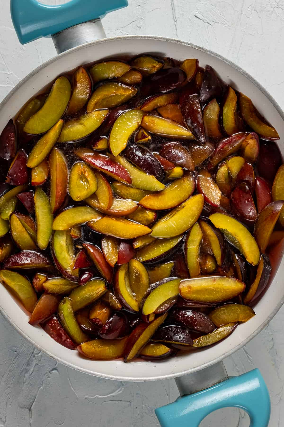 Sliced plums after waiting covered with sugar overnight.