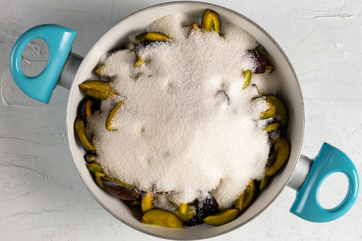 Sliced plums covered with granulated sugar in a white pan.