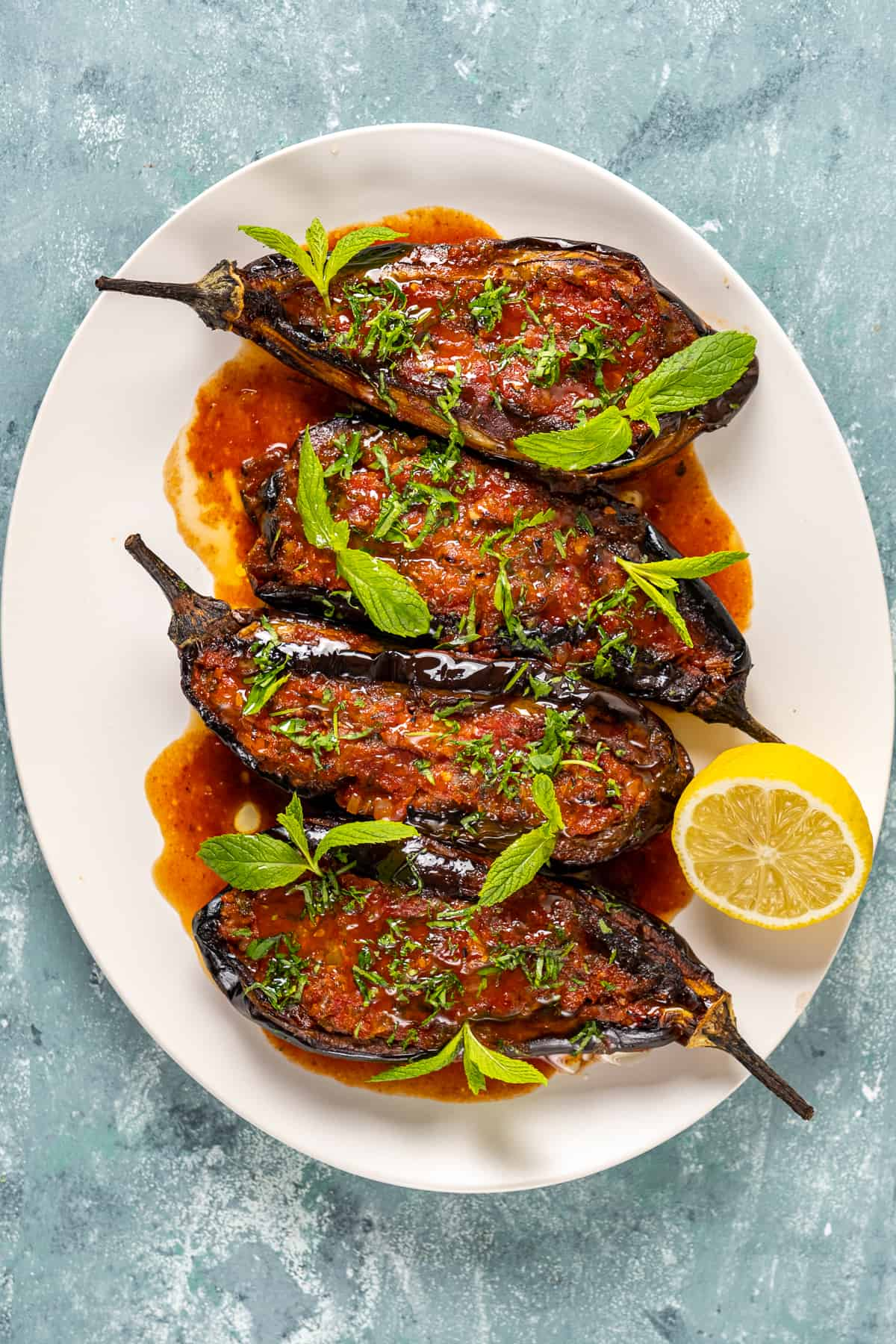 Imam bayildi eggplants served with tomato sauce, herbs and a half lemon in a white oval dish.