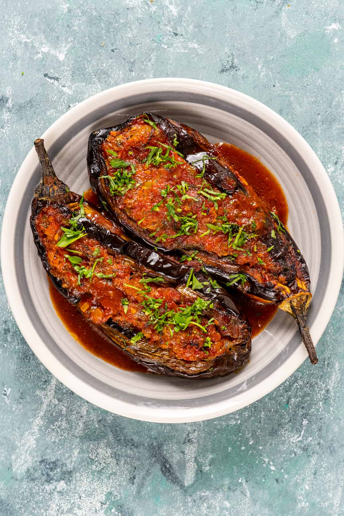 Stuffed roasted eggplants topped with tomato sauce and herbs in a white dish.