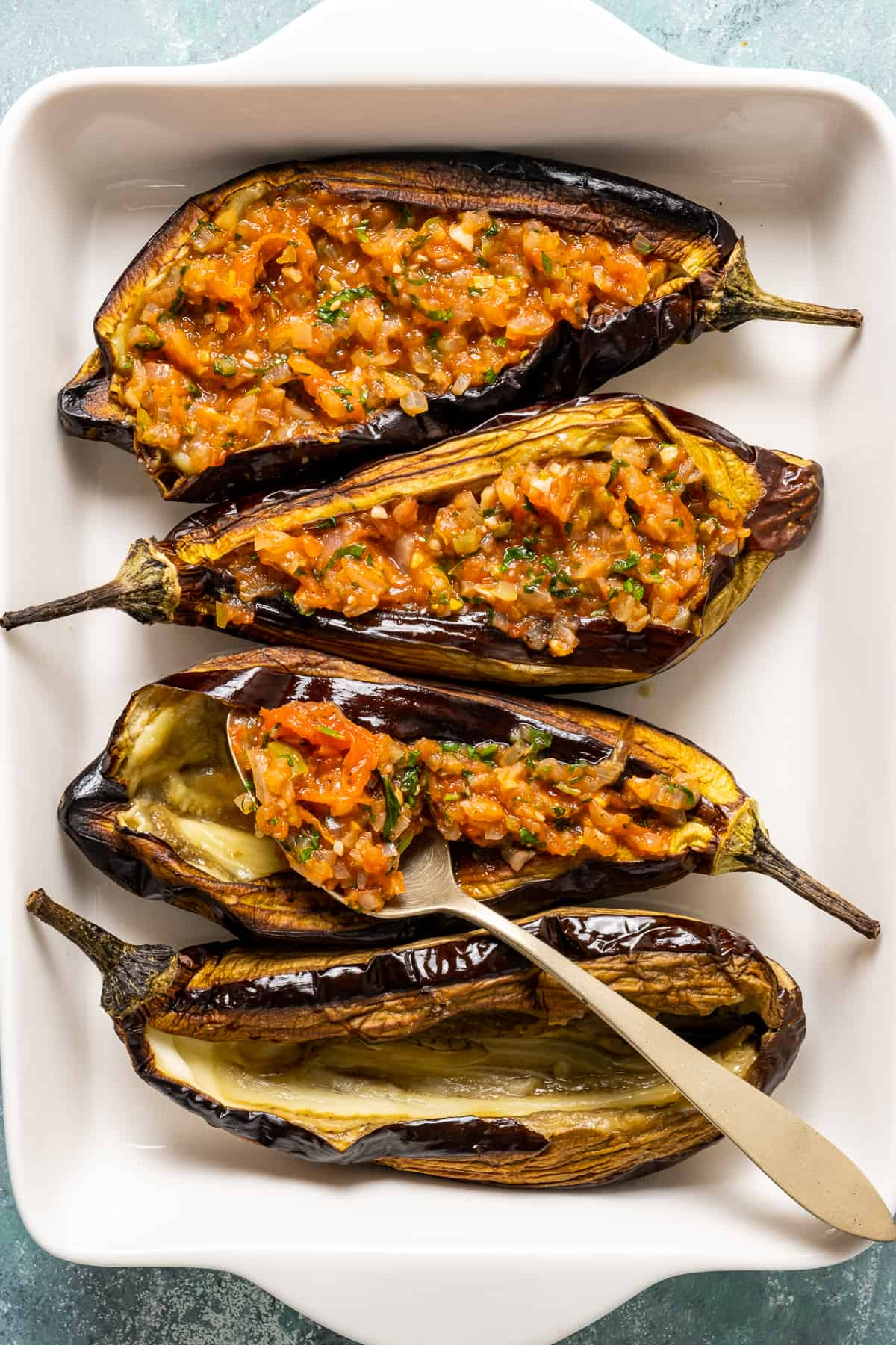 Stuffing roasted eggplants with tomato and onion filling with a spoon.
