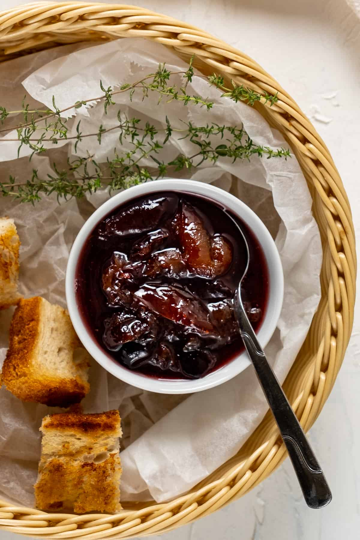 Plum jam in a small white bowl with a spoon in it and toasted mini bread slices and fresh thyme all in a basket.