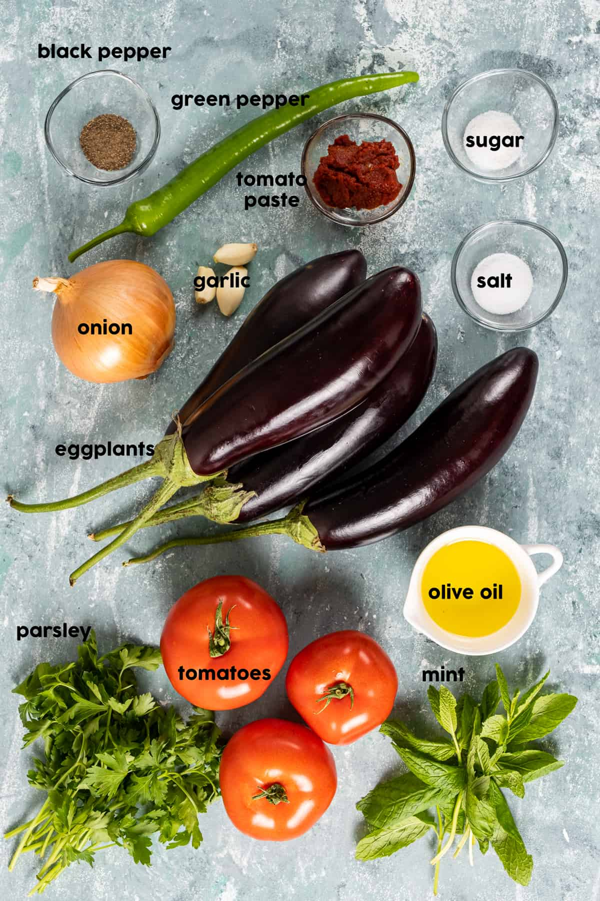 Eggplants, a green pepper, an onion, a bunch of parsley and mint, olive oil, garlic, tomato paste and spices in mini bowls on a grey background.