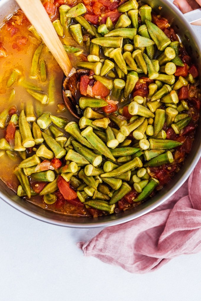 Okras and tomatoes cooking in a pan and a wooden spoon in it.