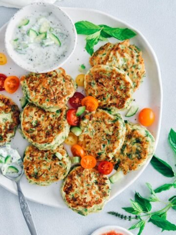 Zucchini fritters on a ceramic plate served with grape tomatoes and yogurt dip