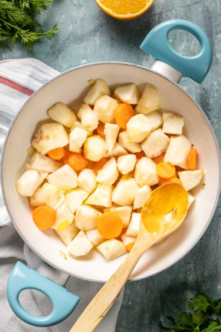 Chopped sunchokes and carrots in a white pan and a wooden spoon inside it.
