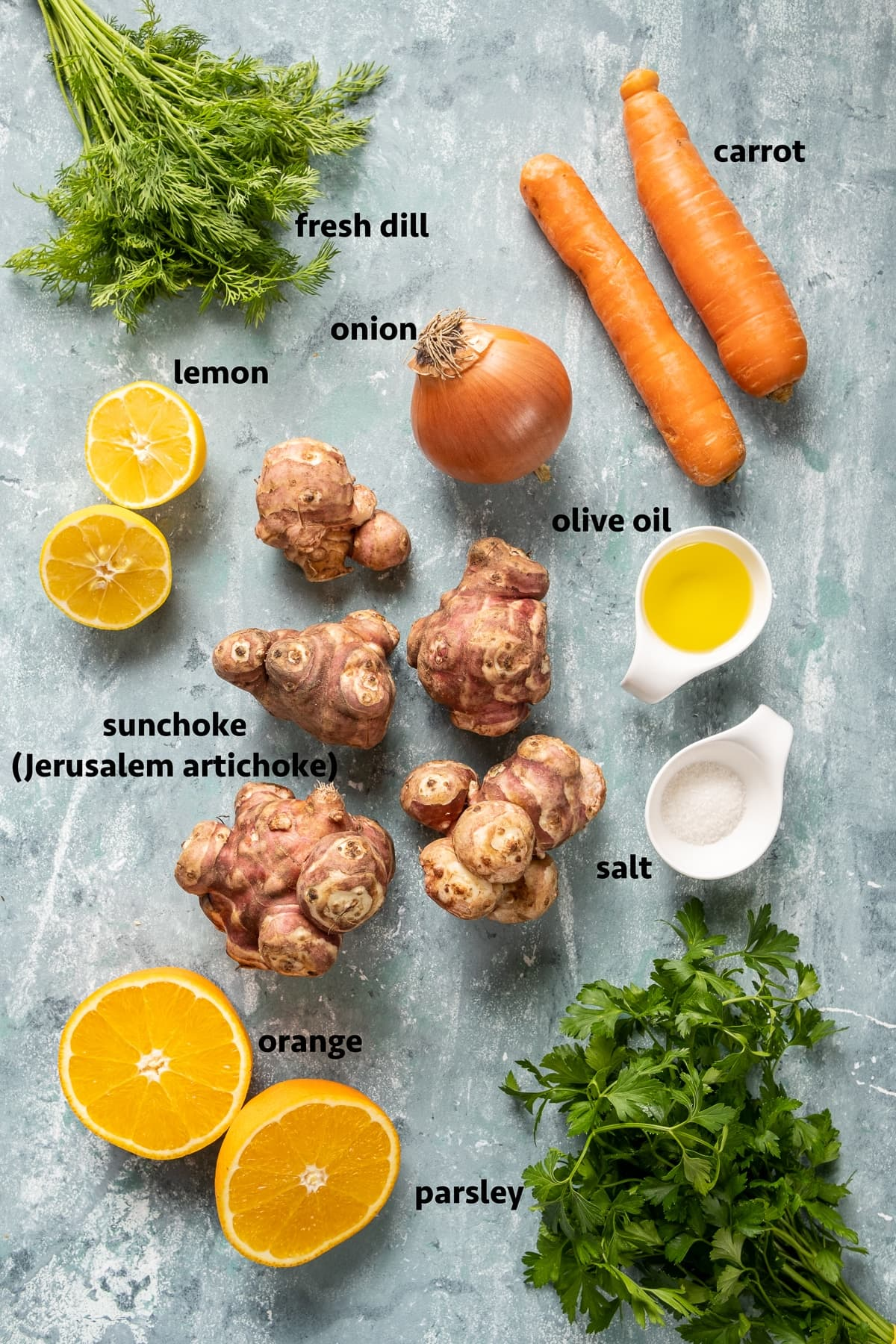 Sunchokes, carrots, onion, halved lemon, halved orange, olive oil, salt, fresh dill and fresh parsley on a light colored background.