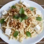 Homemade pasta with cheese, walnuts and fresh basil in a white dish.