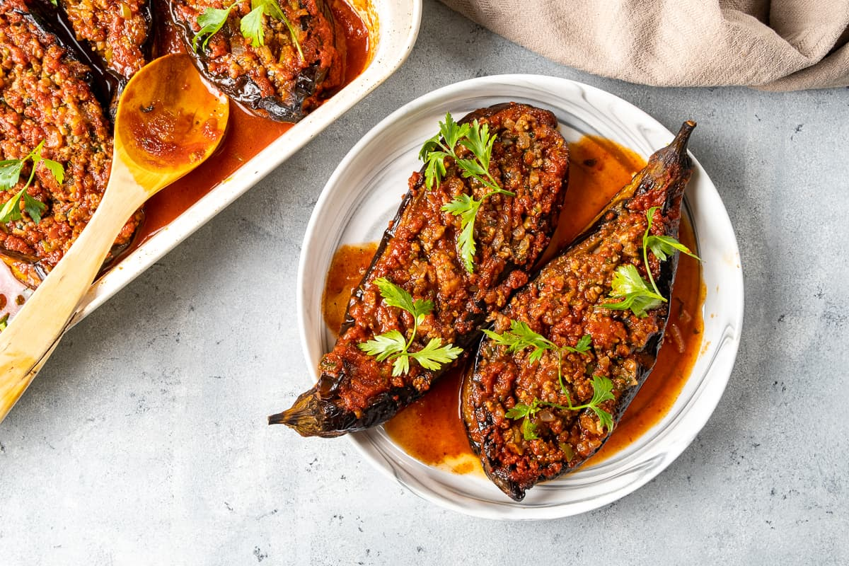 Baked stuffed eggplants served on a white plate and the baking pan on the side.