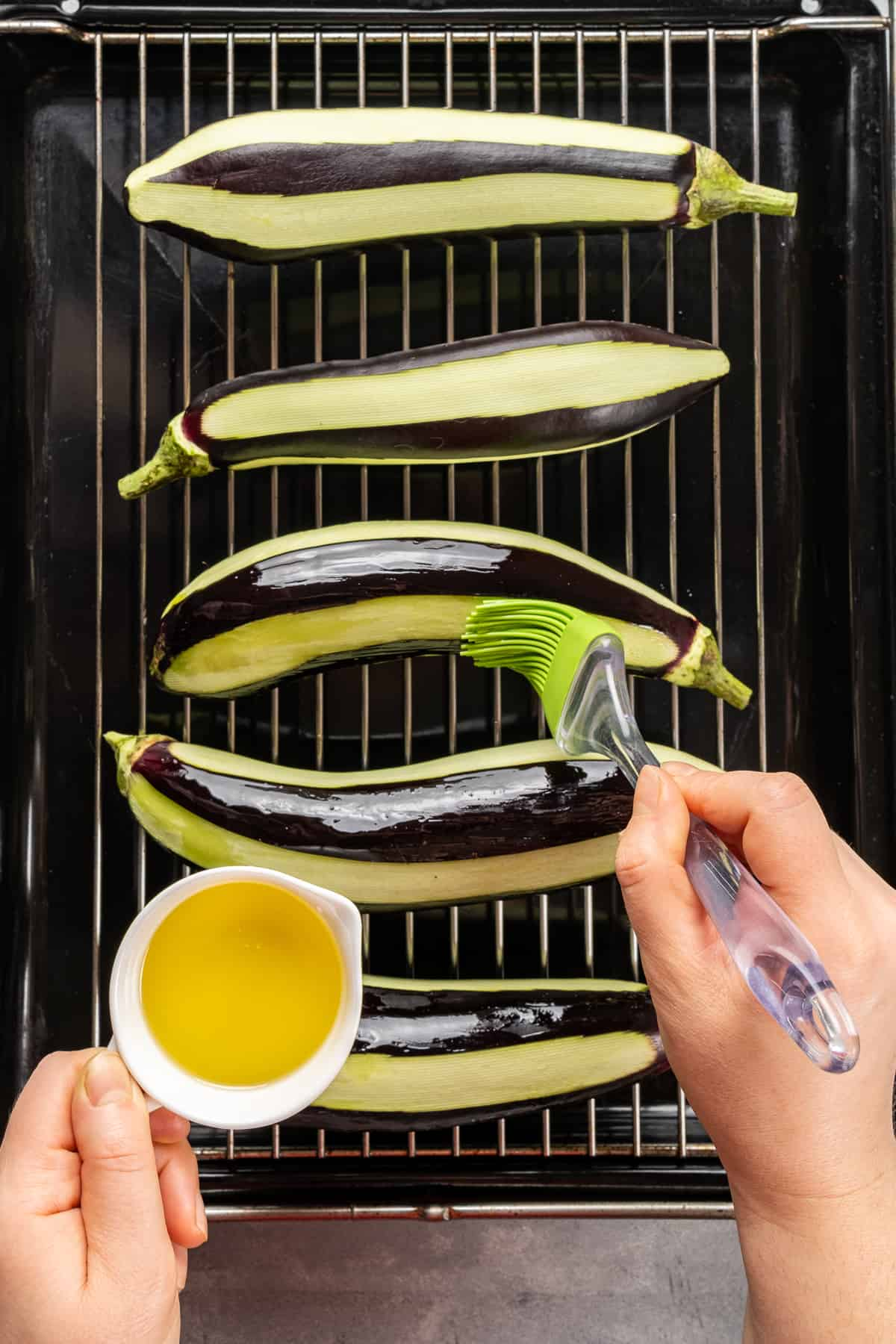 Hands brushing eggplants with olive oil.