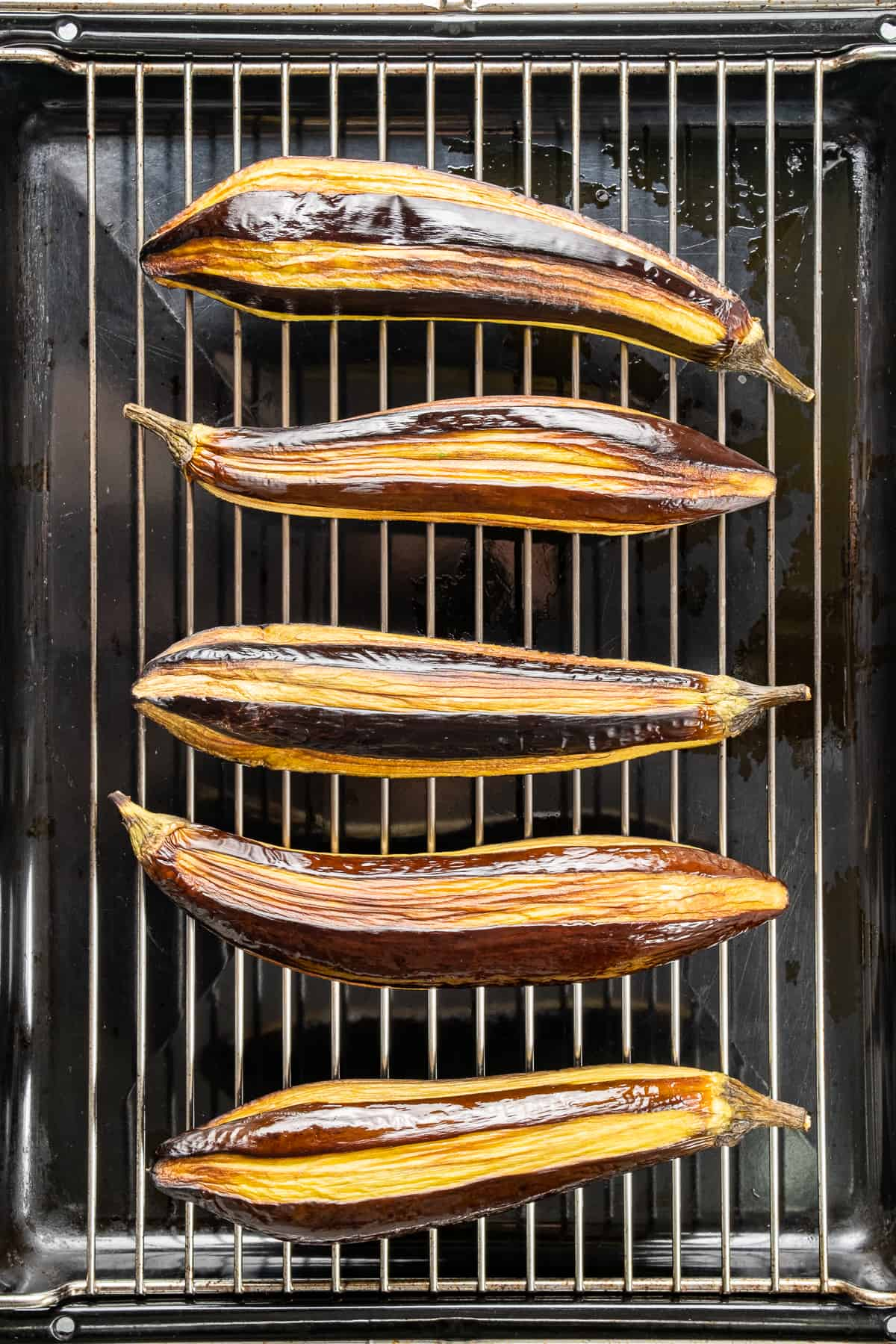 Partly peeled whole eggplants roasted on an oven grill rack.