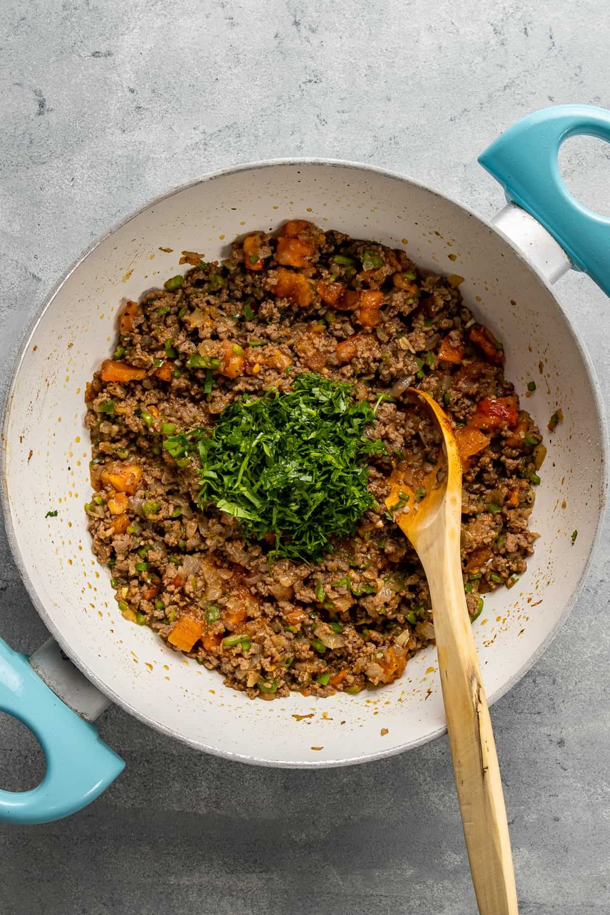 Ground beef filling with tomatoes and parsley in a white pan and a wooden spoon inside it.