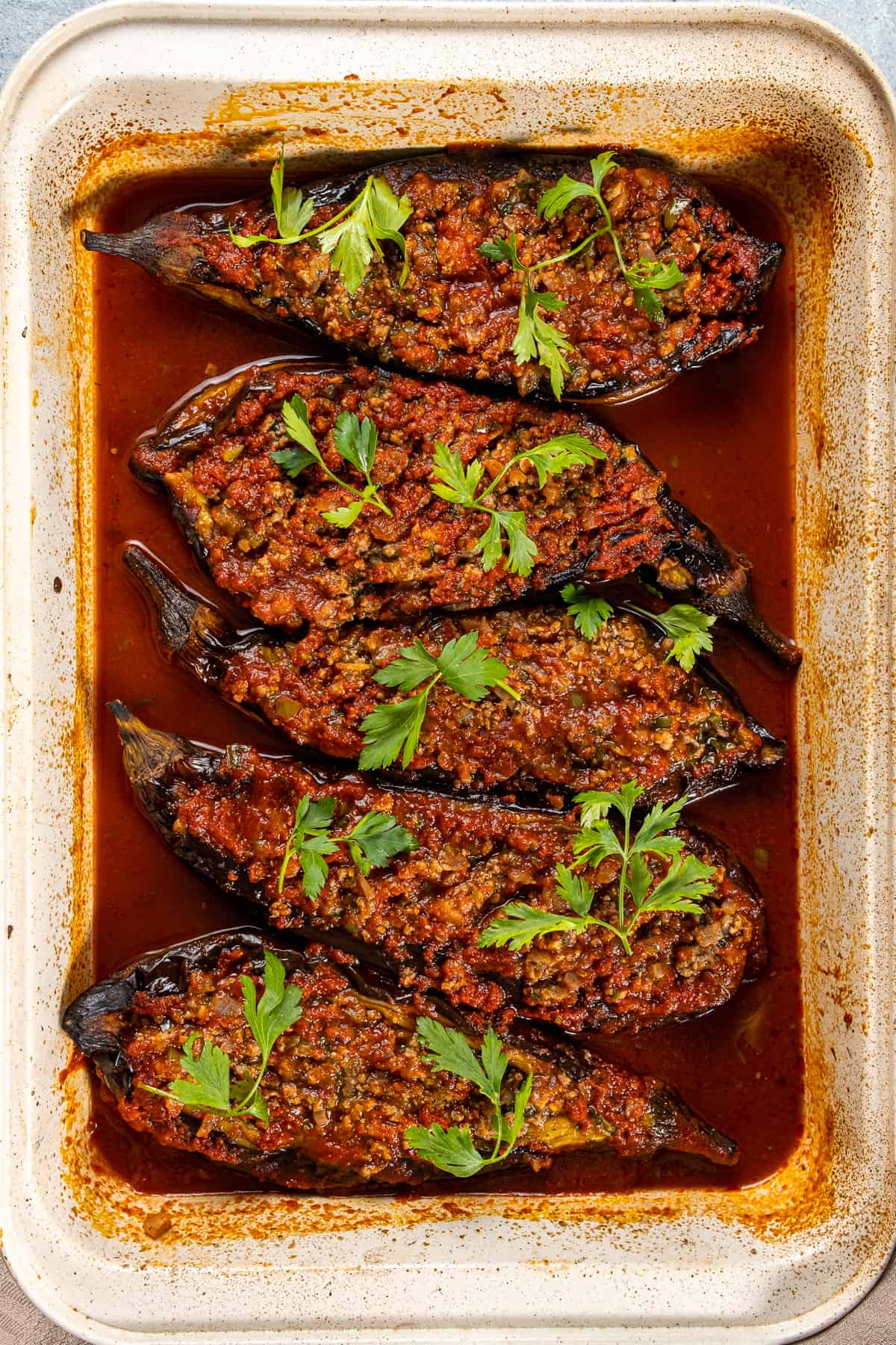 Ground beef stuffed eggplants baked in tomato sauce garnished with parsley in a baking pan.