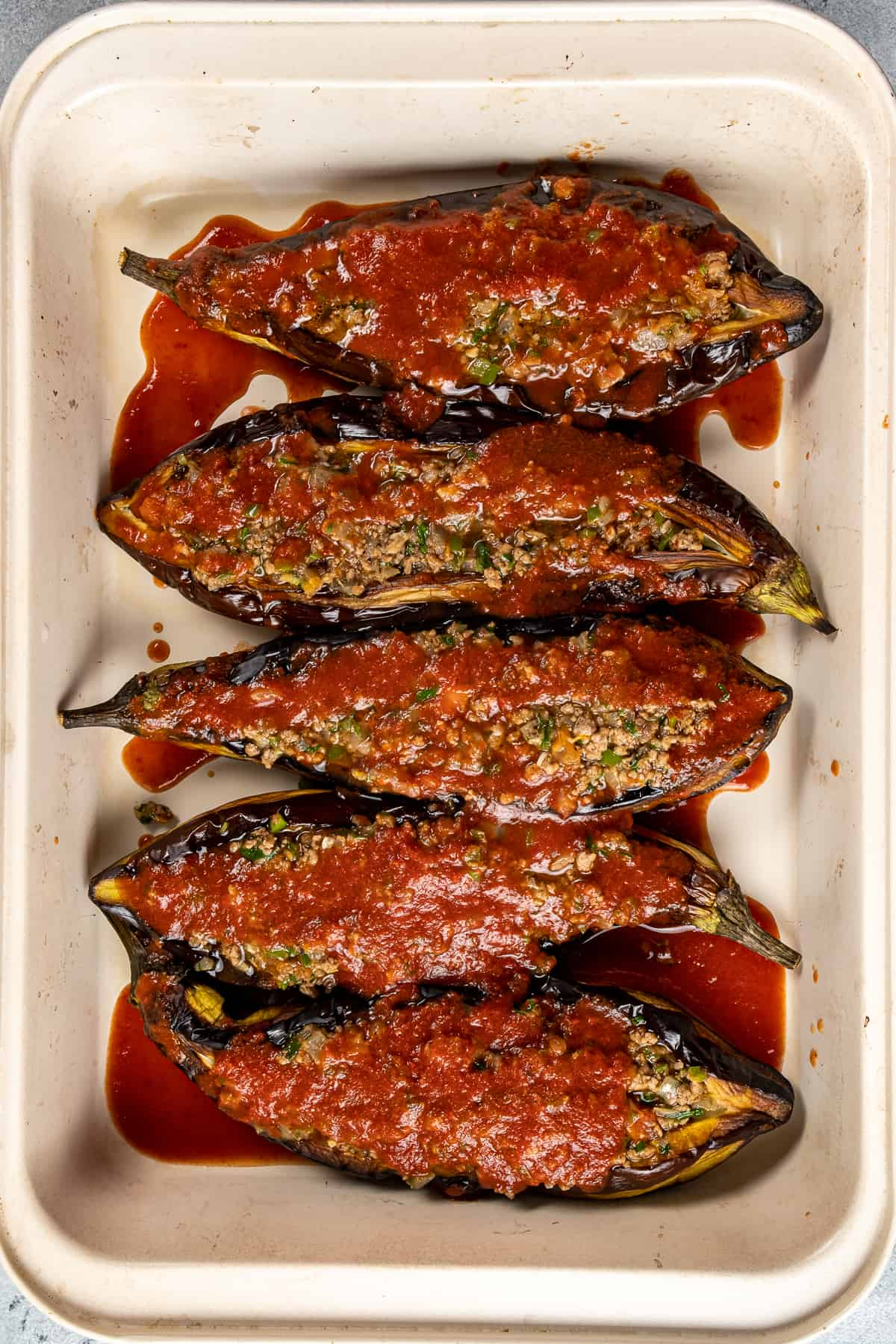 Stuffed roasted eggplants covered with tomato sauce in a baking pan.